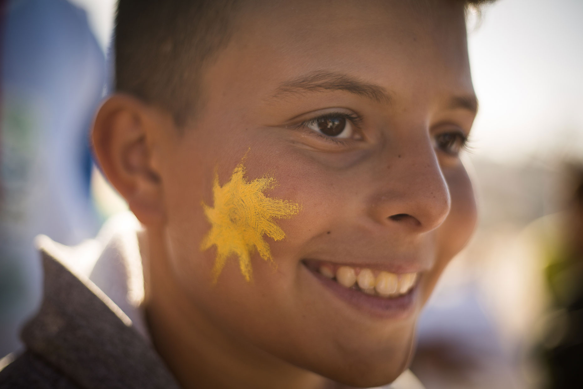 Greenpeace boy with sun on cheek, by Scotland photographer