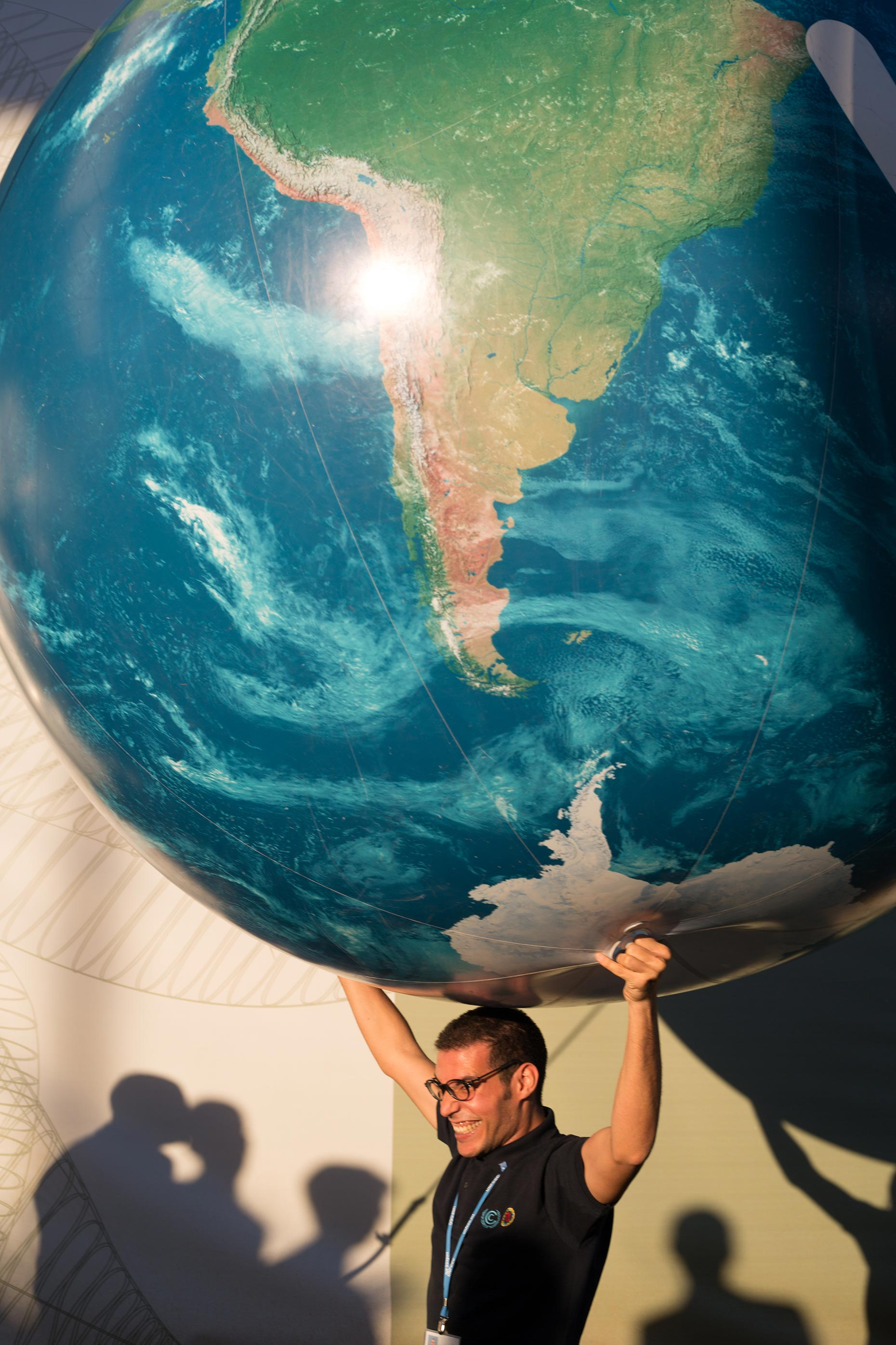 man holding inflatable world globe on shoulders, by Scotland Greenpeace photographer