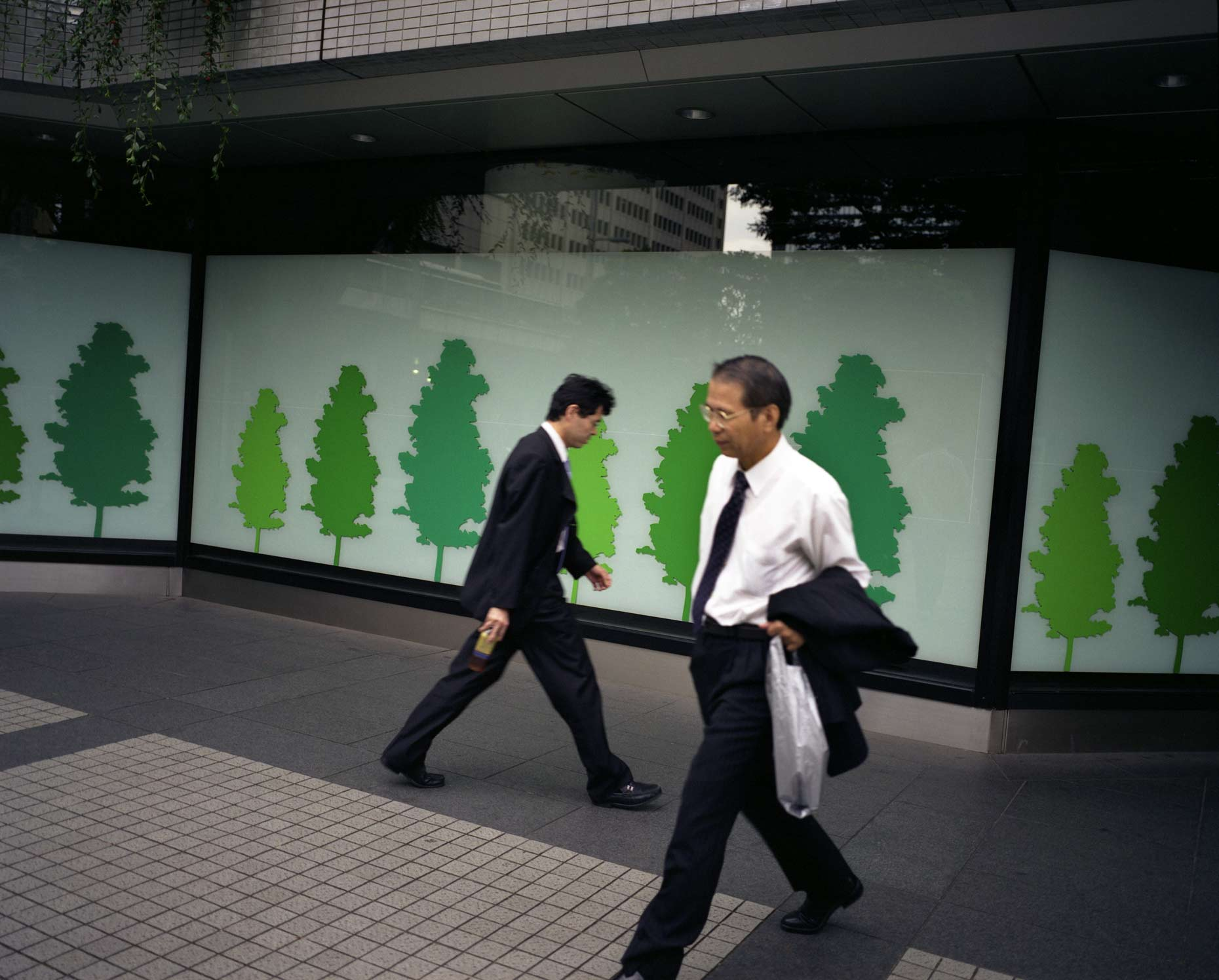 Business men walk past Billboards depicting nature, Tokyo, Japan.