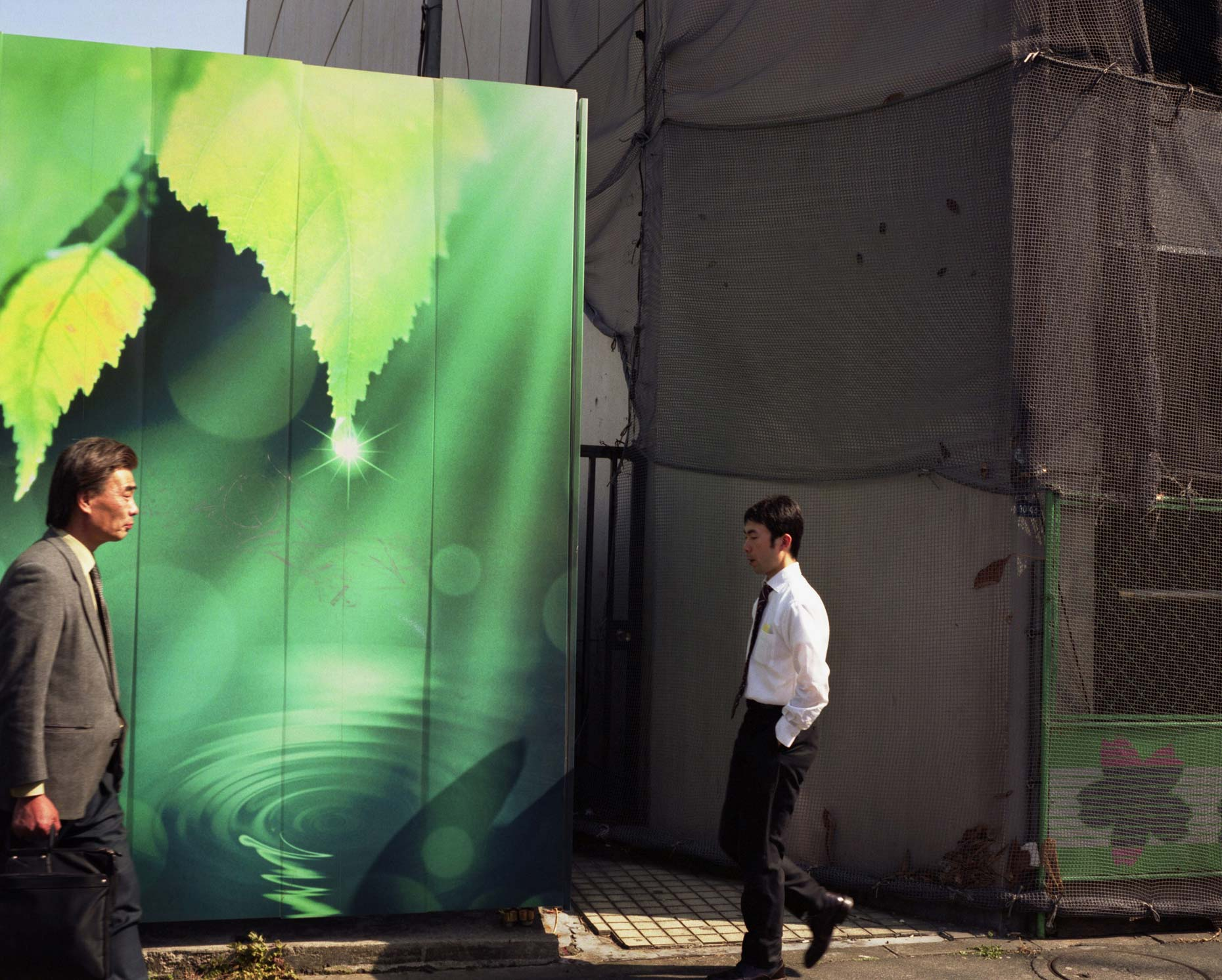 Businessman walking past Billboards depicting nature, Tokyo, Japan.